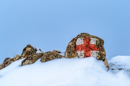 winter blues: Red cross sign in the mountain to guide and prevent.