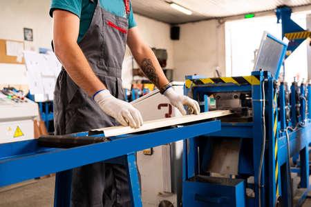 Worker man at factory measures works metal production industrial Foto de archivo