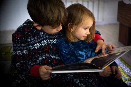 Brother and sister read book in pyjamas feet evening sleep family