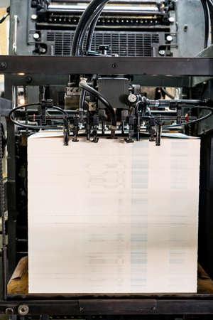 Offset printing machine feeder transfer metallic paper through the feeding table to the printing unit factory Archivio Fotografico