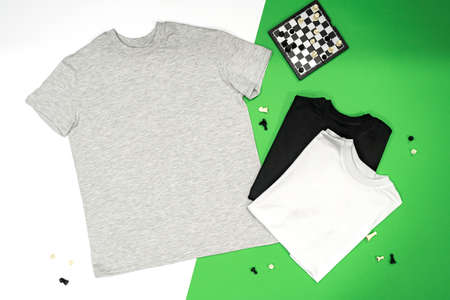 Close-up of the three t-shirts (black, white and gray) on color background redand green