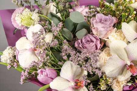 Bouquet of pink roses, alstroemeria flowers orchids. Fresh summer flowers on gray background
