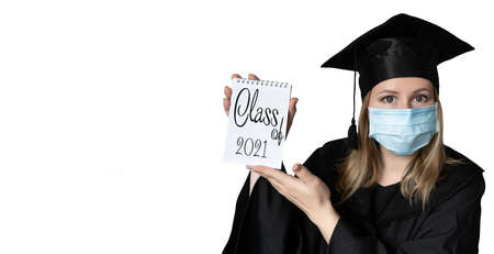 A student in mask is wearing a graduation cape and robe holding blank copy space place concept of the class 2021 coronavirus pandemic of the covid. Graduation student on white background