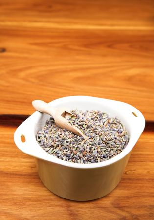 measuring spoon: Ceramic green pot and small wooden measuring spoon with dry lavender flowers on wooden background