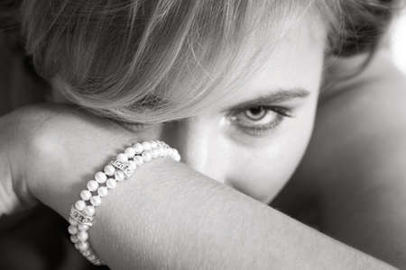 Young woman luring from behind her arm with pearl bracelet