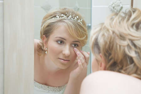 Reflection of a young woman in wedding dress fixing her make-up photo