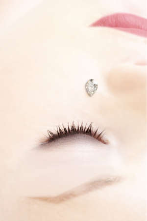 Tear shaped diamond on a cheek of young woman