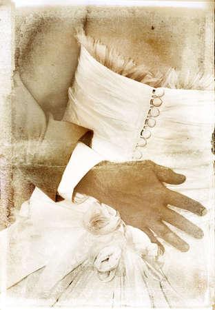 groom�s hand on detailed silk dress overlaid on rich grunge texture