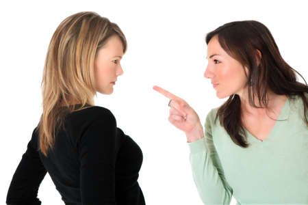 accusation: Neatly dressed brunette pointing accusing finger at a blond woman