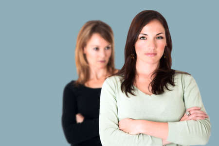 accusation: Confident young brunette with arms crossed and her jealous opponent in the background Stock Photo