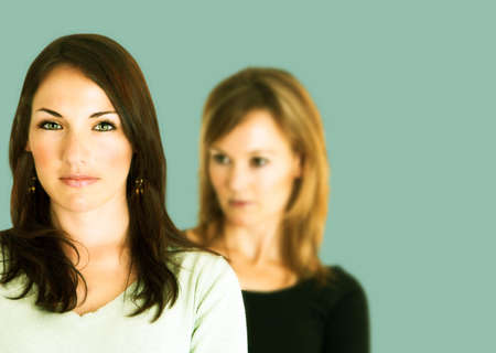 Confident young brunette with arms crossed and her jealous opponent in the background Stock Photo
