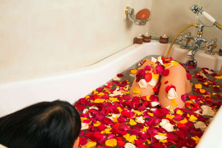 wife of bath: young woman with black hair enjoying rose petal and candlelight bath in a victorian style bath