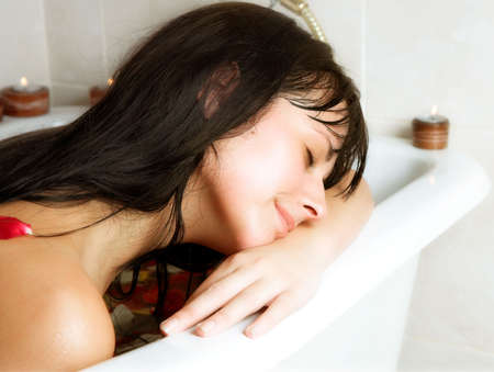 Young woman with long dark hair dreamily resting on her hands on the edge of the bath photo