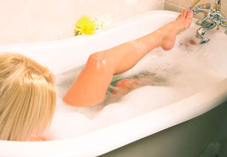 Playful blond girl in a foamy Victorian bath with flowers on the edge Stock Photo - 552087