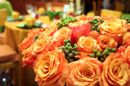 Orange roses in a lush bouquet in a wedding reception venue Stock Photo