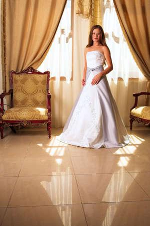loose hair: Bride con capelli allentati lunghi che si levano in piedi in una stanza pienamente decorata in uno stagno di luce naturale Archivio Fotografico