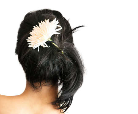 tresses: Back of a young woman with a flower in her black hair