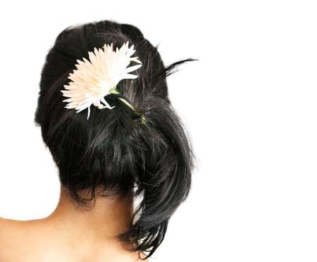 loose hair: Indietro di una donna giovane con un fiore in suoi capelli neri