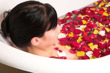 young woman with black hair enjoying rose petal bath photo