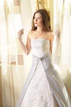 bodas de plata: Preciosa joven novia con cabello largo casta�o y blanco en plata satinado vestido a la ventana de luz natural