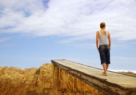 Young woman on old wooden bridge over rocky gorge – view from the back, copy-space over sky Stock Photo