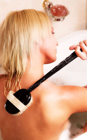 Young blond woman sitting in bath with body brush on her back Stock Photo - 966331