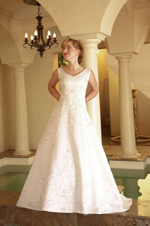 bead embroidery: Beautiful blond bride with short hair; in white v- neck dress; bead embroidery; next to small pool of water
