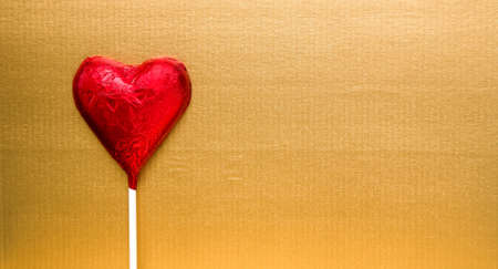 Red heart shape chocolate on lolly stick and golden paper background with copy space photo
