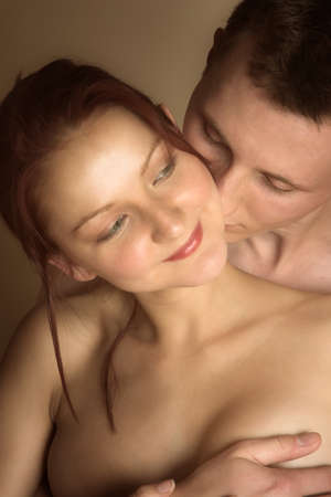 Young couple, man and woman, in loving embrace - focus on man eyes