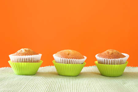 Three carrot muffins in lime green plastic cups against orange wall on table