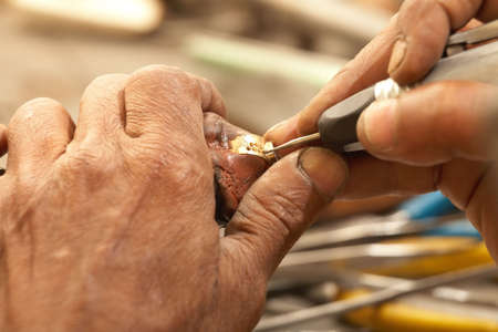 Goldsmith working on an unfinished 22 carat gold ring with his hard working hands