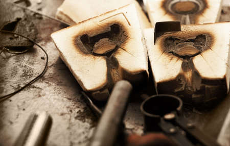 unpolished: Old wooden jewelry molds for casting precious metals in a goldsmith workshop  Stock Photo
