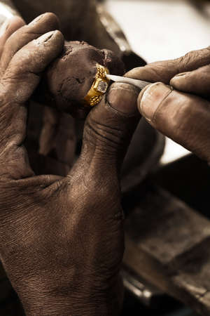Goldsmith working on an unfinished 22 carat gold ring with big diamond with his hard working hands. Shallow DOF - focus on the ring. Fine gold dust on hands and tools