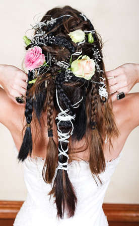 young bride with long brown hair braided with roses and beads in complex design wearing white corset wedding dressr photo