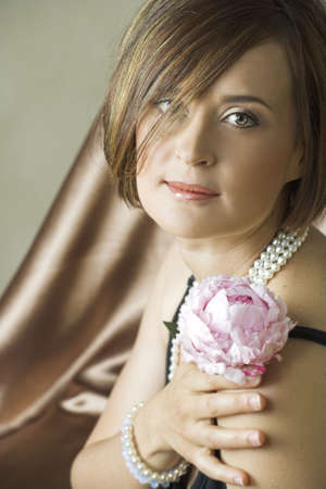 Beautiful young woman with natural make-up and brown hair wearing pearls in her mid 30s, holding pink flower on silk background