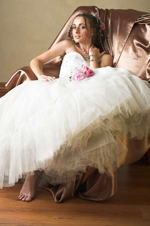 Beautiful happy young bride with long brown hair in white tule petticoat and vinateg and antique accessories sitting on a chair photo