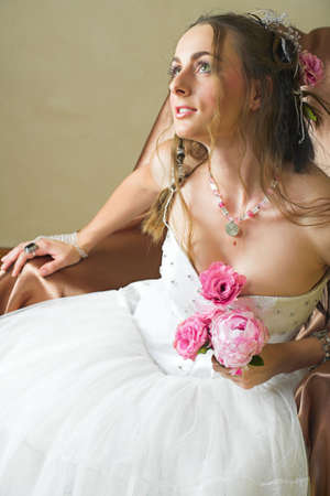 Beautiful happy young bride with long brown hair in white tule petticoat and vinateg and antique accessories sitting on a chair holding pink spring peony  photo