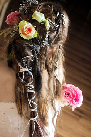 styler: Beautiful young bride with long brown hair in wedding dress holding a small flower bouquet with hair braided in Renaissance styler