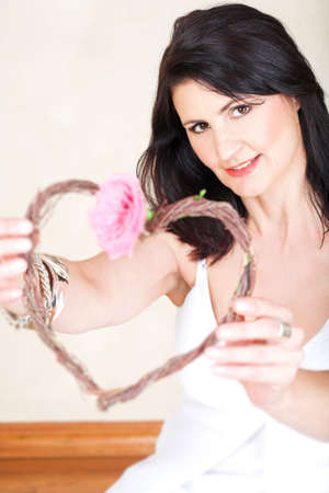 Beautiful happy adult woman with black straight hair and soft natural make-up holding a heart with a flower on Valentines day, in her forties. Focus on the face. Stock Photo