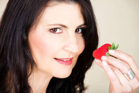 early 40s: Beautiful happy adult woman with black straight hair and soft natural make-up holding a strawberry. Very fine laugh lines and soft wrinkles appropriate to model�s early 40s, visible clear pore texture.
