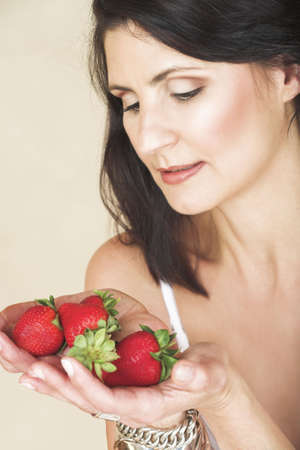 Beautiful happy adult woman with black hair and soft natural make-up in her 40s holding large red strawberries in her hands photo