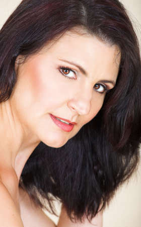 Beautiful happy adult woman with black long straight hair and soft natural make-up in her 40s