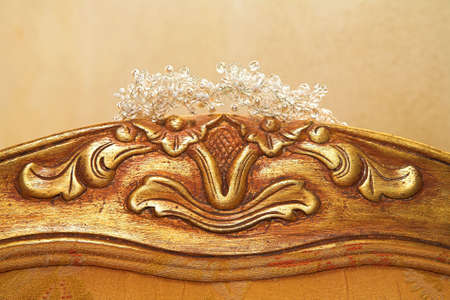 Beautiful crystal and pearl wedding tiara on antique carved chair back Stock Photo