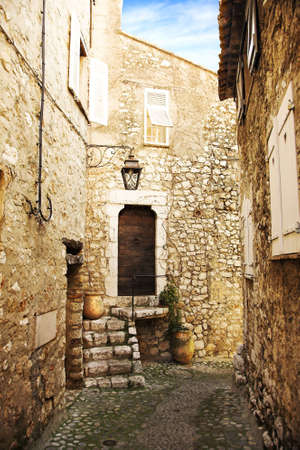 narrow cobble street with sandstone houses in a village of Saint-Paul de Vence, France  photo
