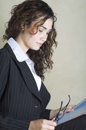 pinstripe: Beautiful young brunette businesswoman with long curly hair, wearing pinstripe suit  Stock Photo