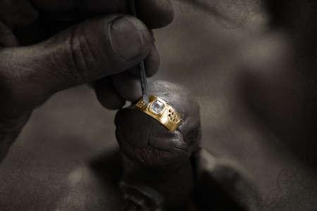 artesano: Goldsmith en un trabajo sin terminar 22 quilates de oro con gran anillo de diamantes con su duro trabajo en manos grunge papel bakground