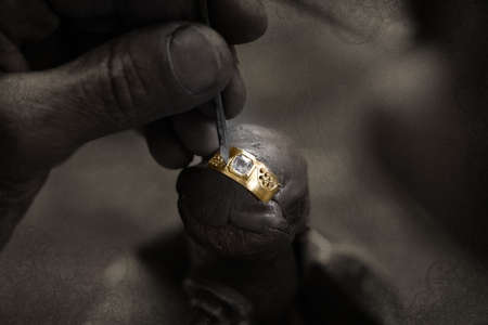 jeweler: Goldsmith working on an unfinished 22 carat gold ring with big diamond with his hard working hands on grunge paper bakground