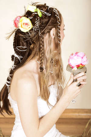 Beautiful young bride with long brown hair in wedding dress holding a small flower bouquet with hair braided in Renaissance styler