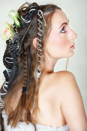 Beautiful young bride with long brown hair in wedding dress and hair braided in Renaissance style photo