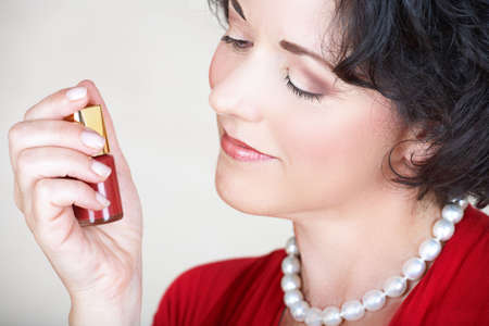 woman in her nid 30s or early 40s holding nail polish bottle in her hand and smiling photo